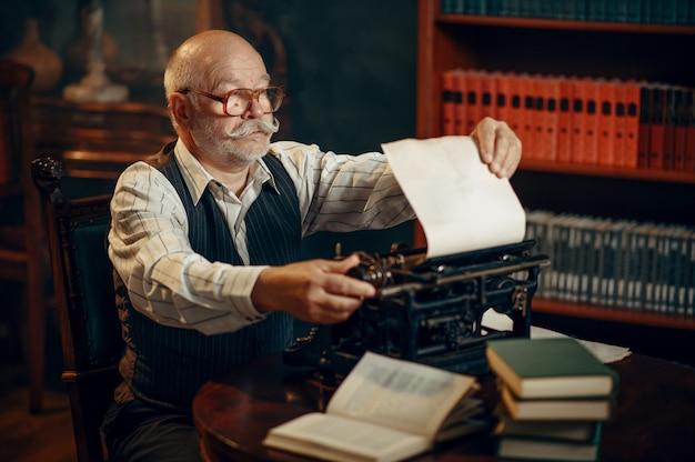 노인 작가는 집 사무실에있는 빈티지 타자기에 종이를 넣습니다. 노인은 연기와 함께 방에 문학 소설을 씁니다.
