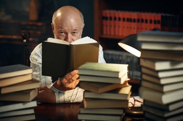 노인 작가는 홈 오피스에서 책 더미와 함께 테이블에서 읽습니다. 안경을 쓴 노인이 연기와 영감을 받아 방에 문학 소설을 쓴다