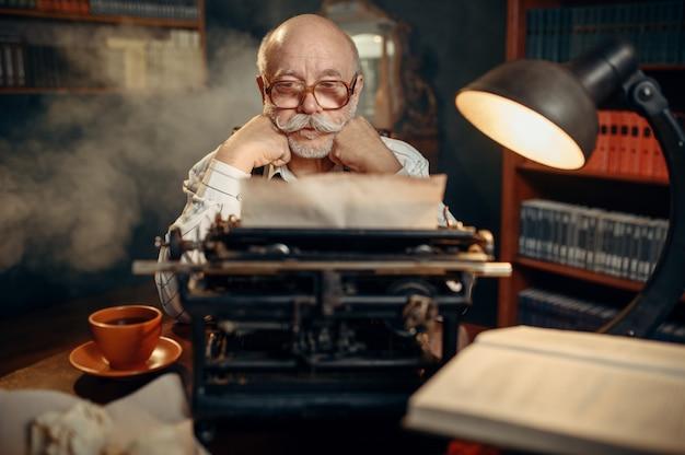 Пожилой писатель думает на старинной пишущей машинке