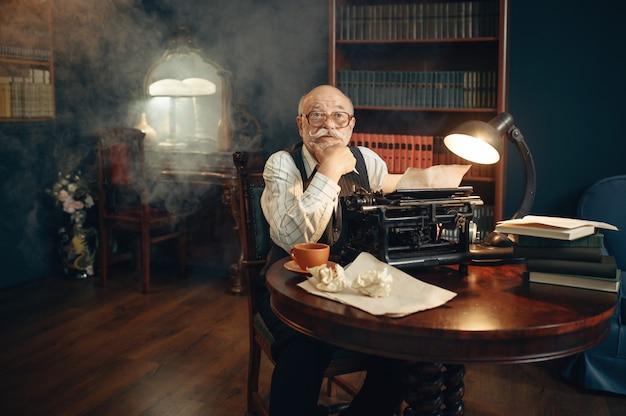 노인 작가는 그의 홈 오피스에서 빈티지 타자기로 작업합니다. 안경에 노인이 연기가 나는 방에 문학 소설을 씁니다.