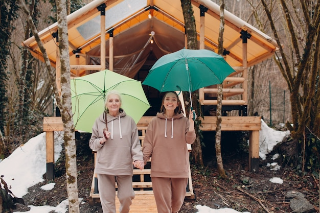 Elderly and young adult women with umbrella at glamping camping tent modern autumn vacation lifestyl...