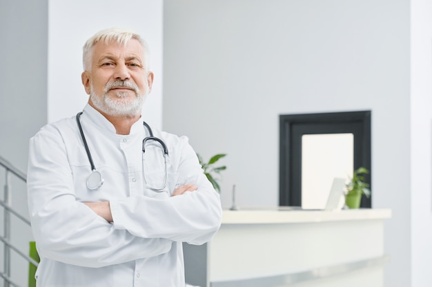 腕を組んでコートを着た高齢医師。