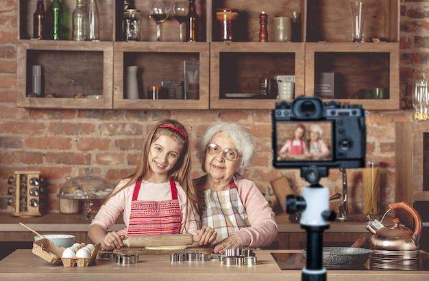 素敵な孫娘と一緒にいるおばあちゃんは、めん棒を使ってカメラを見て生地を広げます
