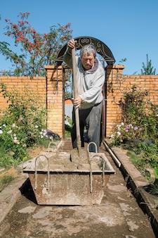 老人は庭の小道を注ぐためにセメントをこね、庭の建設工事をします。