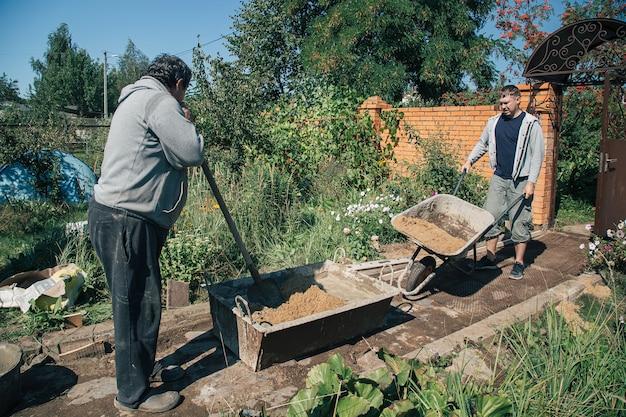 老人は庭の小道を注ぐためにセメントをこねる
