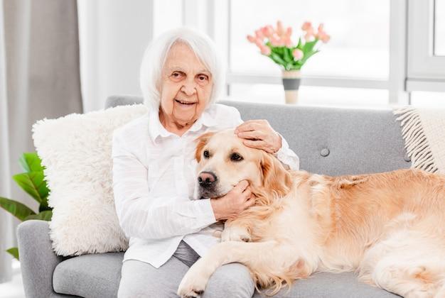 골든 리트리버 강아지를 안고 화창한 날 집에서 카메라를 바라보는 할머니