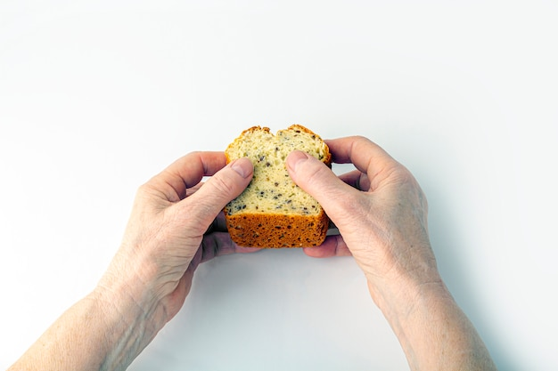 Eldery woman's hands hold small freshly baked homemade whole-grain bread on white background. helping hand concept, toned image
