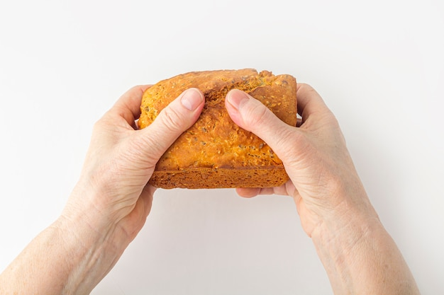 Eldery woman's hands hold small freshly baked homemade whole-grain bread on white surface. helping hand concept. copy space for text