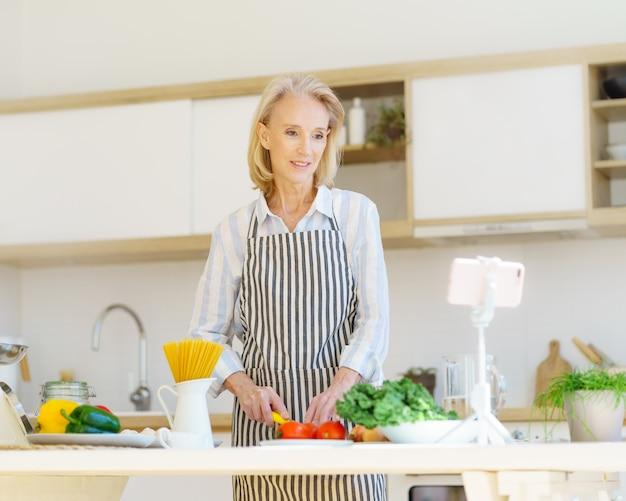 Пожилая женщина-видеоблогер записывает онлайн-урок кулинарии или видео-рецепт во время приготовления еды дома в