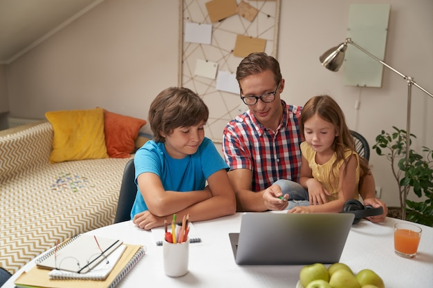 Elearning cute little kids with father wearing eyeglasses looking at laptop son and daughter