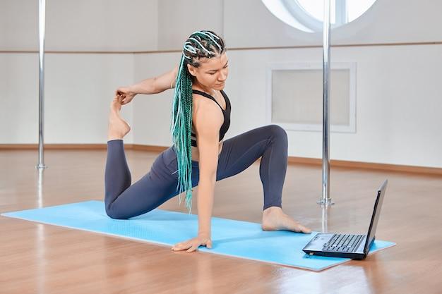 ストレッチのeラーニングまたは遠隔教育、ラップトップコンピューターを使用してオンラインで体の柔軟性のレッスンを見ている中年女性。