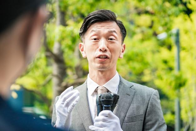 屋外の有権者に街頭で演説する選挙候補者