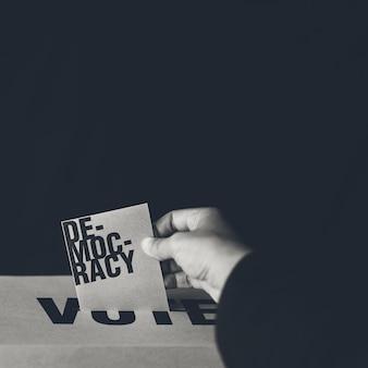 Вставка избирательной карты в ящик для голосования, концепция демократии, черно-белые тона