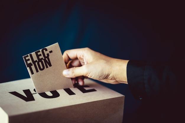 Election card insert in vote box, democracy concept, retro tone