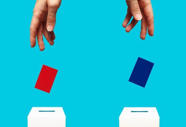 선거 개념 여자 손은 흰색 투표 상자에 파란색 카드를 넣습니다