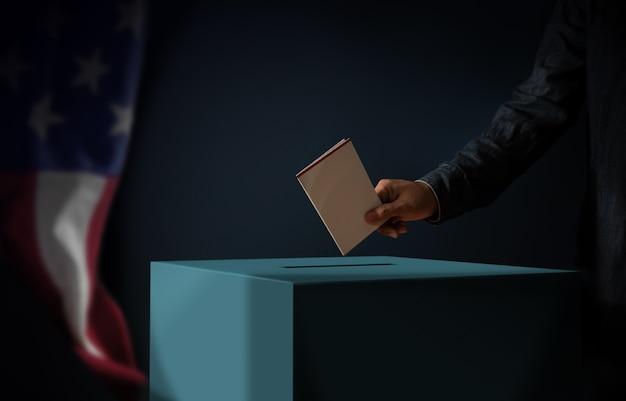 День выборов в соединенных штатах америки концепции. человек, опускающий избирательную карточку в урну для голосования. флаг сша висит на стене. темный кинематографический тон