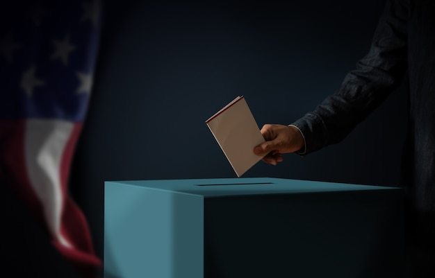 Election day in united states of america concept. person dropping a ballot card into the vote box. usa flag hanging on the wall. dark cinematic tone