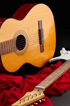 Электрические и классические акустические гитары на красной ткани, никто. струнный музыкальный инструмент, электро и живой звук, музыка, оборудование для музыканта