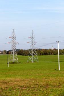 Электрические и высоковольтные опоры в поле с зеленой травой на фоне голубого неба