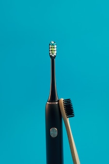 Электрическая и деревянная зубная щетка на синем фоне
