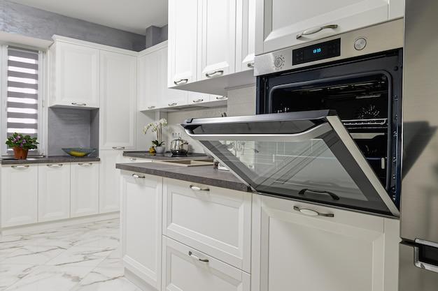 Электрические приборы, такие как кофеварка эспрессо, бутербродница и духовка, в современном минималистичном интерьере белой кухни.