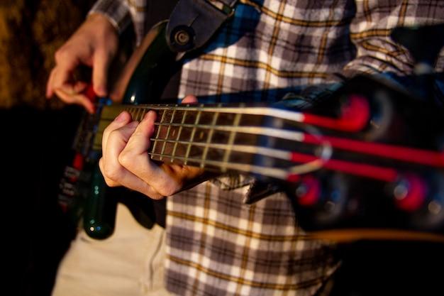 Electric bass guitar player, closeup photo with soft selective focus