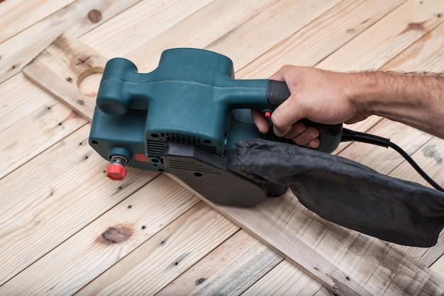 電気ベルトサンダー、男性の手で研磨機。薄茶色の木製テーブルでのワークピースの処理。閉じる