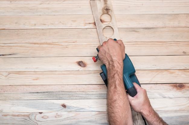 Электрический ленточный шлифовальный станок, шлифовальный станок в мужской руке. обработка заготовки на светло-коричневом деревянном столе. прямо выше, скопируйте пространство