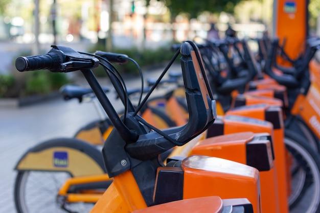 도시 도시의 전기 자전거 스테이션 사용자 대여를 위해 준비된 자전거 핸들을 닫습니다.