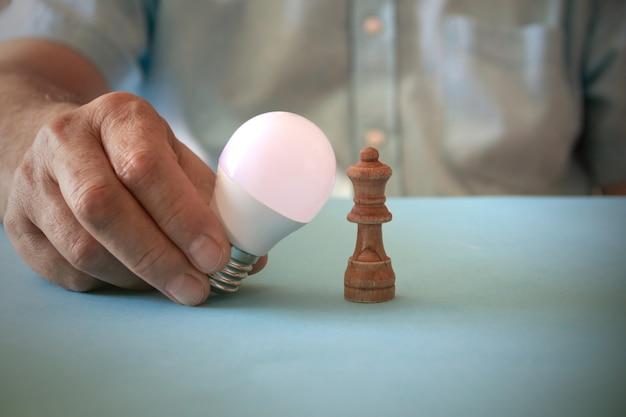 電球とチェスの駒を使った電気事業のコンセプト。スペースをコピーします。セレクティブフォーカス。