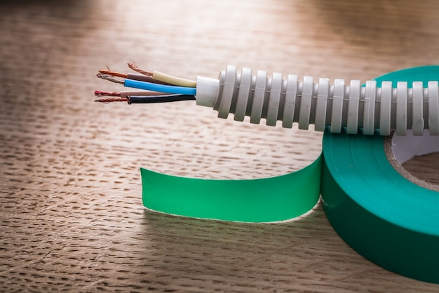 Electric cable in corrugated pipe on roll of green insulating tape