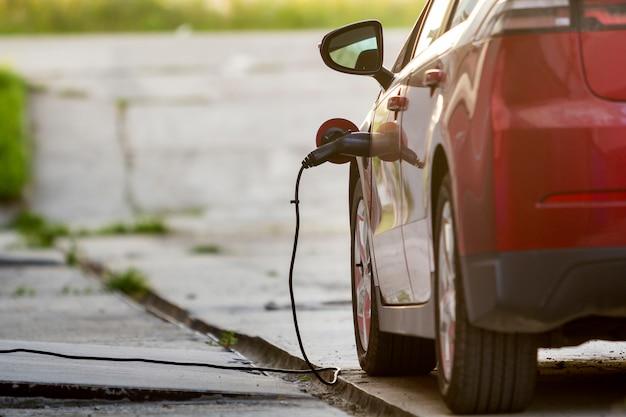 明るい日当たりの良い通りで充電されている電気自動車。充電ケーブルがソケットに差し込まれています。現代の技術コンセプト。