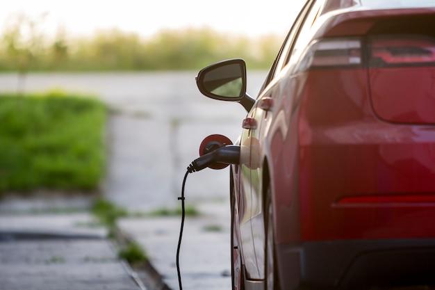 밝고 맑은 거리에서 충전되는 전기 자동차. 충전기 케이블이 소켓에 연결되었습니다. 현대 기술 개념입니다.