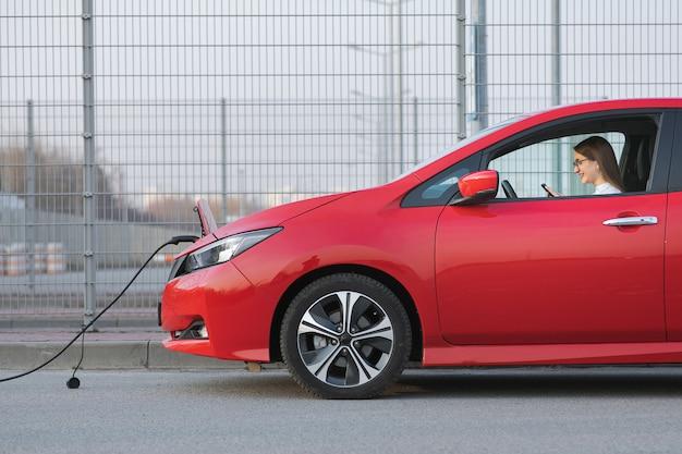 거리에서 충전하는 전기 자동차. 스마트 폰 및 대기 전원 공급 장치를 사용하여 백인 소녀는 자동차의 배터리를 충전하기 위해 전기 자동차에 연결합니다.