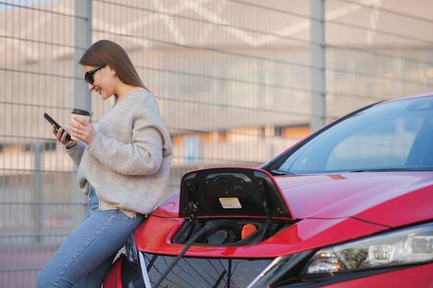 거리에서 충전하는 전기 자동차. 생태 자동차 연결 및 충전 배터리. 스마트 폰을 사용하고 전원 공급 장치를 기다리는 동안 커피 음료를 사용하는 소녀는 충전을 위해 전기 자동차에 연결