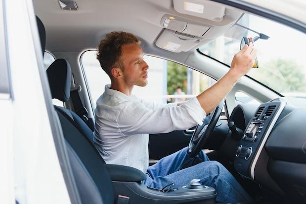 Водитель электромобиля - концепция биотоплива зеленой энергии. мужчина за рулем. человек за рулем нового экологически чистого транспортного средства. молодой мужчина-владелец гордится уверенно, глядя на камеру, концепция водителя такси.