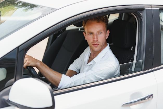 전기 자동차 운전사 - 녹색 에너지 바이오 연료 개념. 바퀴 뒤에 남성입니다. 새로운 친환경 차량을 운전하는 남자 젊은 남성 소유자는 카메라, 택시 운전사 개념을 보고 자신감을 갖고 있습니다.