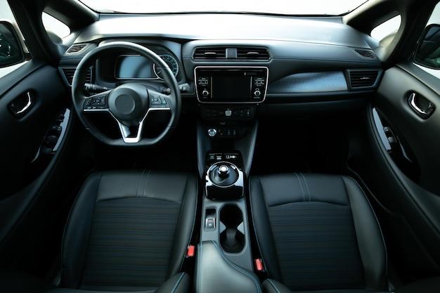 ドアのハンドルの電気自動車内部の詳細。窓のコントロールと調整。フロントシート、運転席と助手席、テキスタイル、窓、ドアパネル、コンソールを備えた車内