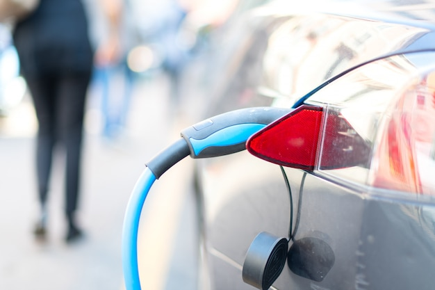 An electric car is charged with energy by a road dispenser
