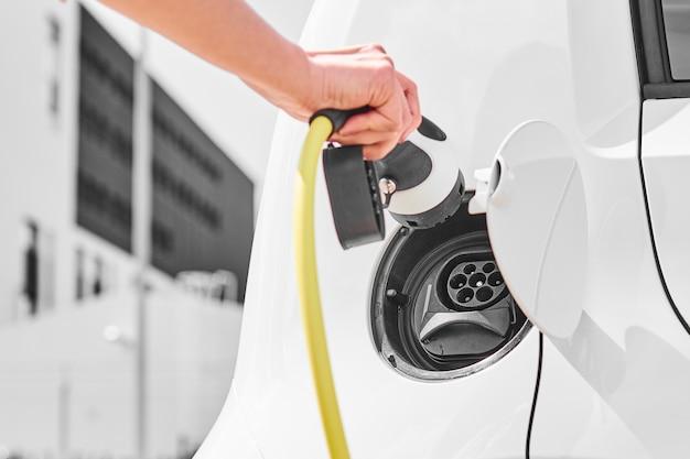 Зарядка блока питания электромобиля на зарядном устройстве. крупный план вверх по руке женщины, вставляя вилку зарядного устройства в электромобиль.