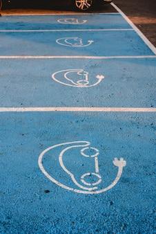 電気自動車。電気充電ステーションの駐車場の床に描かれた看板。