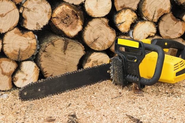Электрическая цепная пила возле аккуратно уложенных пиленых деревьев. электроинструмент для обработки дерева.