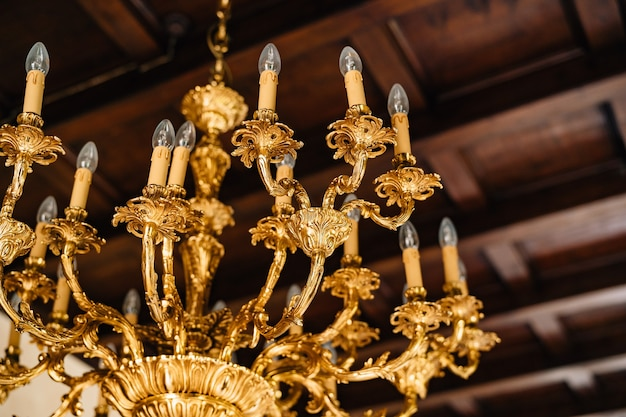 Electric chandelier with bulbs antique golden chandelier in the interior of an old villa