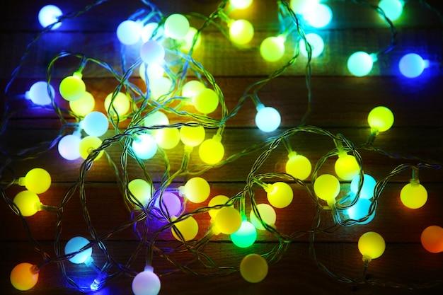 木製の背景に電気クリスマス花輪