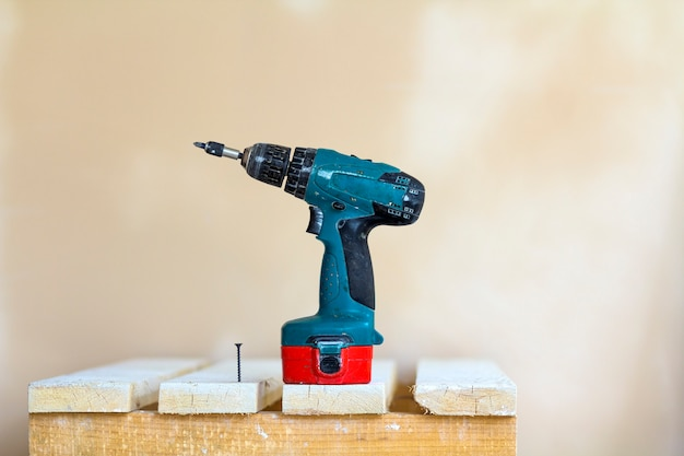 Electric cordless screwdriver and one screw close-up