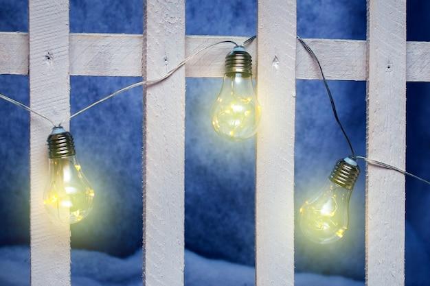 Электрические декоративные лампочки на деревянном стилизованном заборе