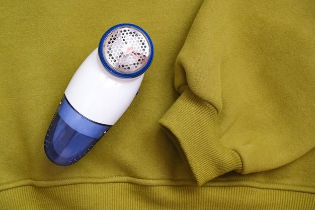 生地の質感の毛や毛羽を取り除くための電気装置。ウール用シェーバー。ニットセーターを背景にペレットを取り除く機械。