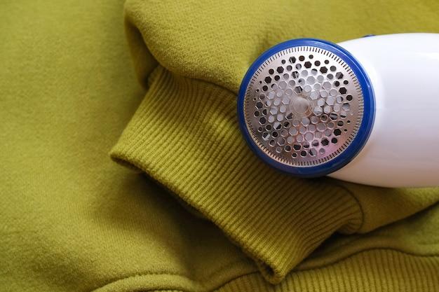 직물 질감의 털과 보풀을 제거하는 전기 장치. 양모용 면도기. 니트 스웨터의 배경에 대해 알약을 제거하는 기계.