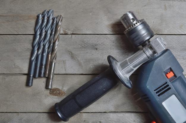 木製の表面で作業するための電気ドリルとツール。上からの眺め。