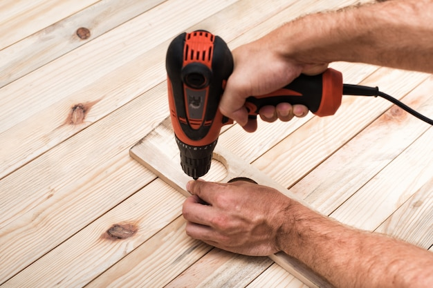 Electric drill screwdriver in male hand. tightening screw, processing workpiece on light brown wooden table.